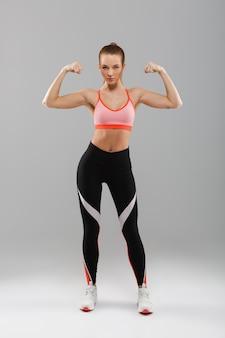 Полная длина портрет серьезной молодой спортивной девушки