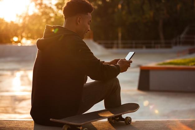 Молодой африканский человек с помощью мобильного телефона