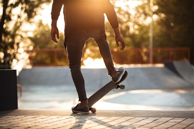Молодой африканский человек делает скейтбординг на открытом воздухе