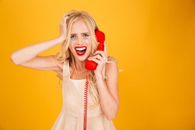 Грустно плачет кричать молодая блондинка разговаривает по телефону.