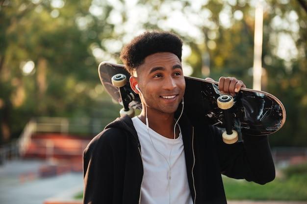 スケートボードを持って若い幸せなスケートボーダー男