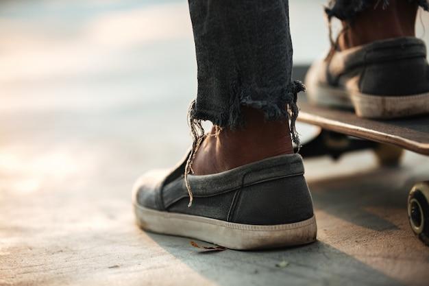 立っているスケートボーダーの足のクローズアップ