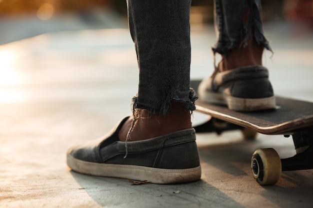スケートボーダーの足のスケートのクローズアップ