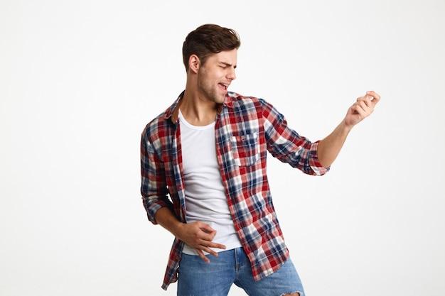 Портрет радостного молодого человека, играющего на гитаре