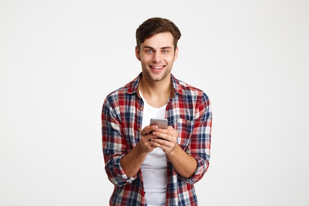 携帯電話を保持している陽気な若い男の肖像