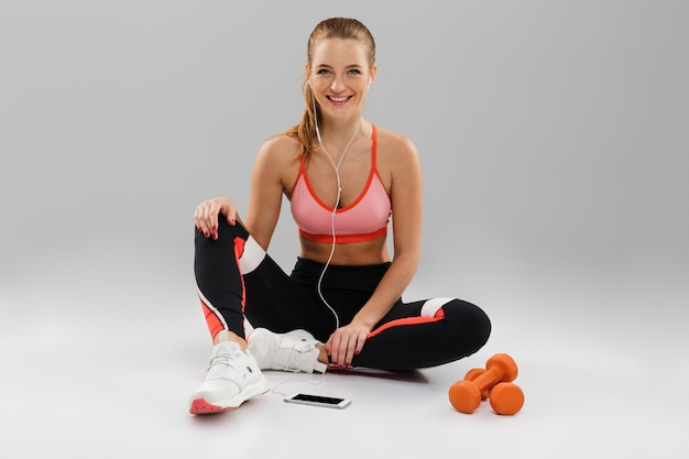 Портрет улыбающейся молодой спортсменки, слушающей музыку
