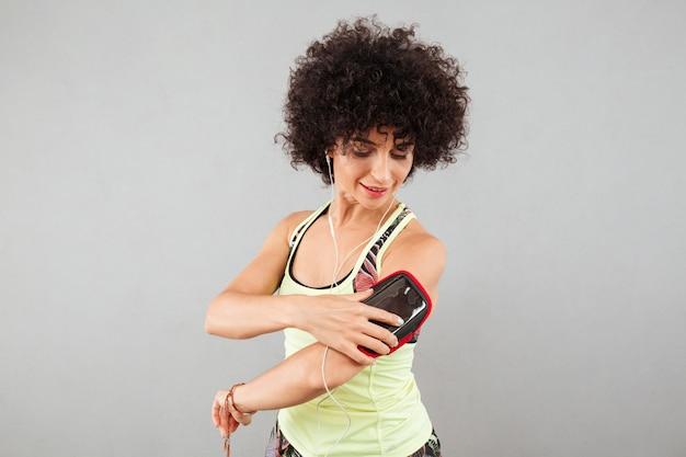 腕章にスマートフォンを使用して巻き毛のフィットネス女性