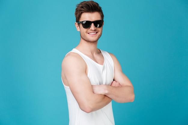 Солнечные очки молодого человека нося смотря камеру