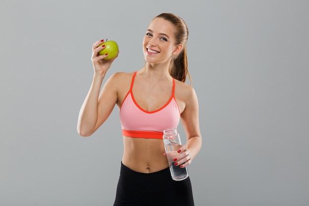 Портрет улыбающегося здоровая спортивная девушка держит зеленое яблоко