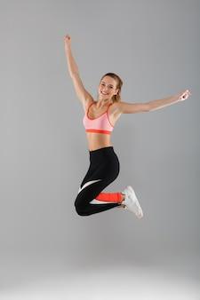 Полная длина портрет счастливого улыбающегося спортсменка празднует