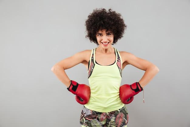 腰に腕を保持しているボクシンググローブのスポーツ女性の笑みを浮かべてください。