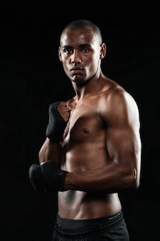 Фотография сосредоточенного красивого молодого сильного афроамериканского боксера, позирующего