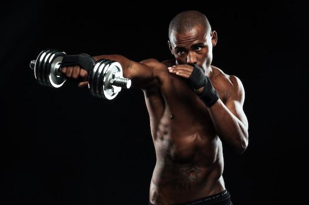 Афроамериканский спортивный мужчина позирует как борьба с гантелями