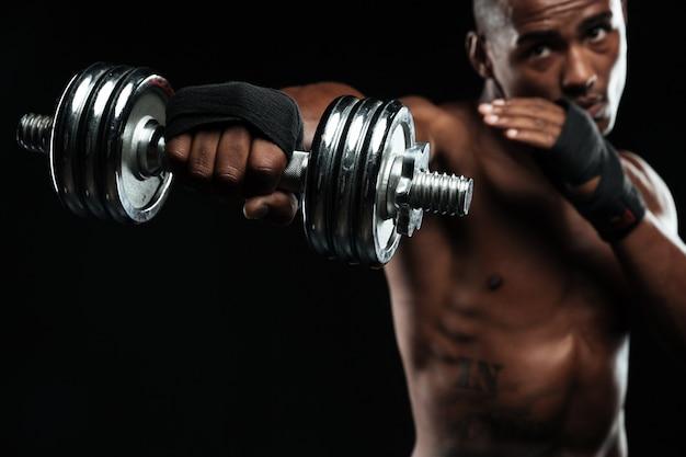 ダンベルでアフリカ系アメリカ人のボクサーのトレーニング