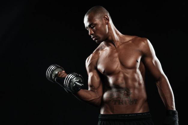 Полуголый молодой афроамериканский спортсмен поднимает гантели