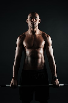 バーベルを保持している筋肉の若いアフロアメリカンの男の肖像