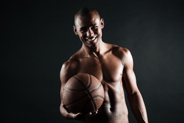 Улыбающийся молодой афро-американский баскетболист, держа мяч