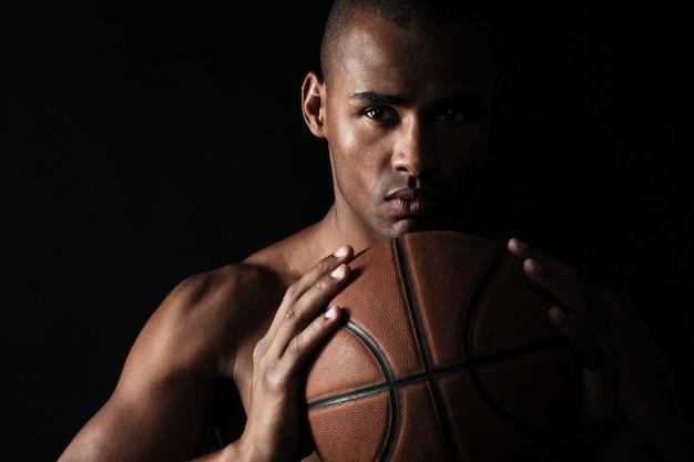 Фотография крупного плана серьезного афроамериканского баскетболиста, держащего шар двумя руками