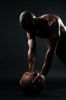 ボールに腕立て伏せ運動をしているアフロアメリカンバスケットボール選手の肖像画