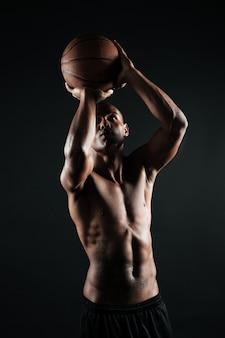 バスケットにボールを投げる準備をして若いアフロアメリカンバスケットボール選手