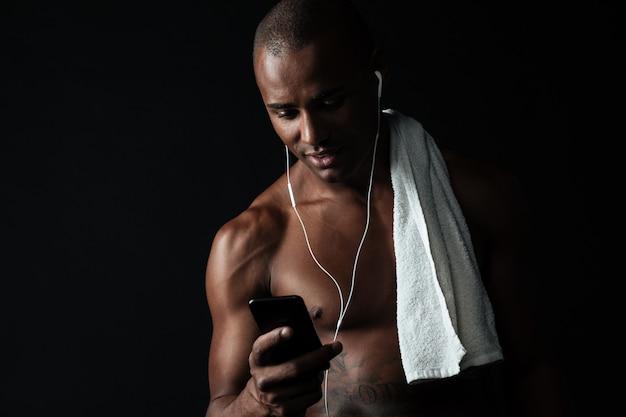 Портрет красивый спортивный мужчина держит мобильный телефон после тренировки