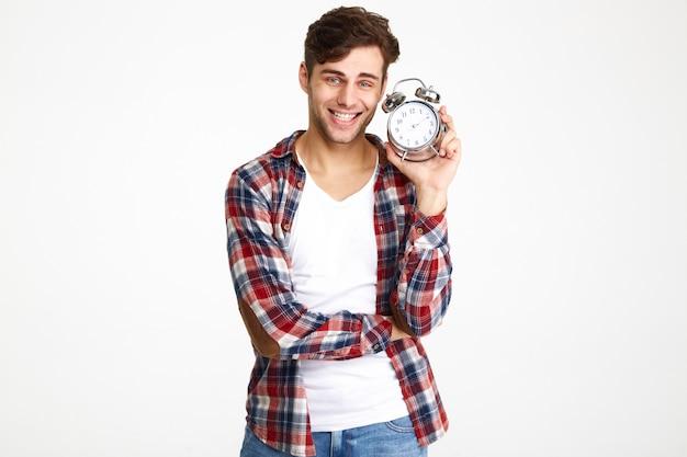 目覚まし時計を示す幸せな笑みを浮かべて男の肖像
