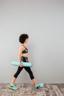 Молодая курчавая спортивная женщина гуляет со спортивным ковриком