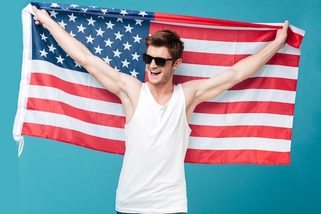 青の分離保持アメリカの国旗の上に立っている若いハンサムな男のイメージ。よそ見。