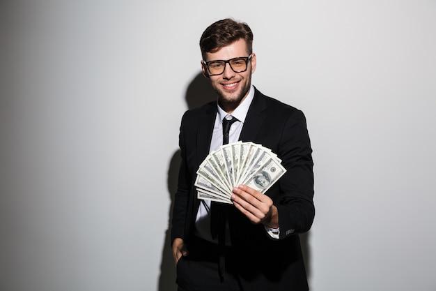 お金の束を示すフォーマルな服装で陽気な男