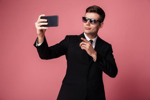 Сконцентрированный молодой бизнесмен делает селфи по мобильному телефону.