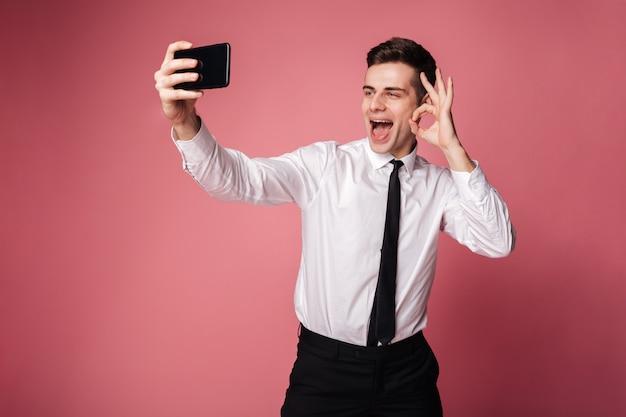 Жизнерадостный молодой бизнесмен показывая одобренный жест.