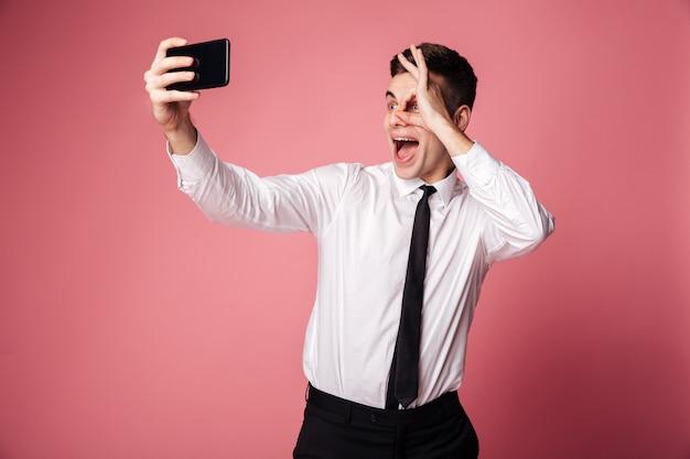Забавный взволнованный молодой бизнесмен делает селфи по мобильному телефону