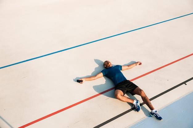 Портрет взгляд сверху вымотанного молодого африканского человека фитнеса