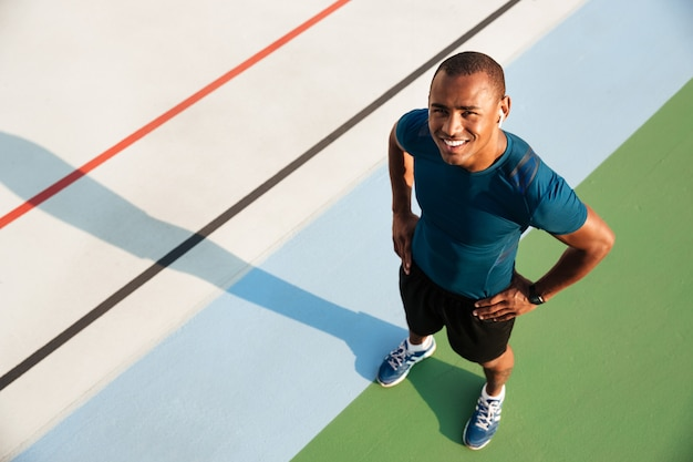 Портрет взгляд сверху усмехаясь мышечного афро американского человека