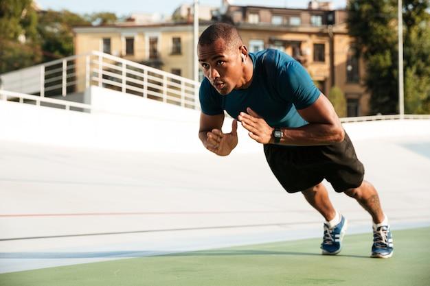 腕立て伏せを行うフィットのアフロアメリカンスポーツマンの肖像画