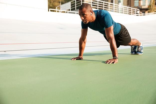 集中した筋肉のアフロアメリカンスポーツマンの肖像画