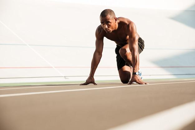 Молодой африканский бегун начиная и готовясь бежать