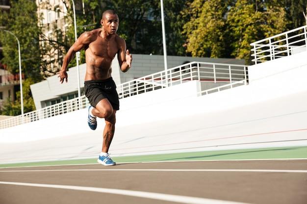 Фотография молодого афро-американского спортсмена, бегущего по беговой дорожке на открытом воздухе