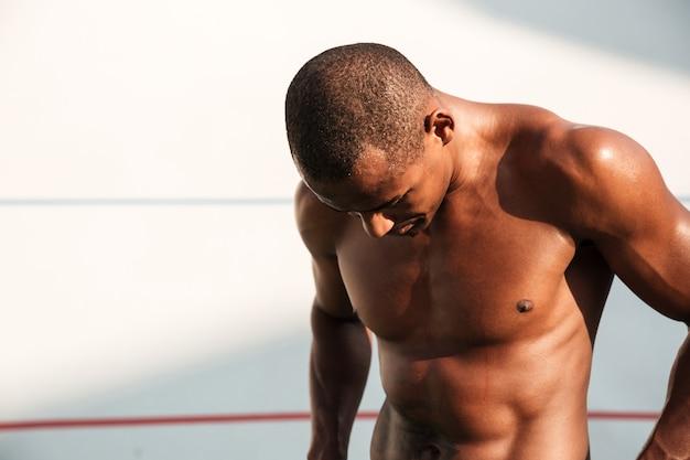 汗をかいたハンサムなアフリカスポーツ男、トレーニングの後休憩のクローズアップの肖像画