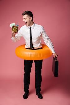 Счастливый эмоциональный молодой бизнесмен с резиновым кольцом.