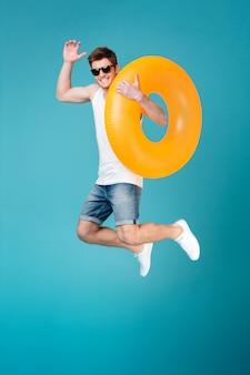 インフレータブルリングを押しながらジャンプのサングラスで幸せな興奮した男