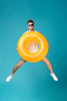 Счастливый возбужденный человек в темных очках держит надувное кольцо и прыгает