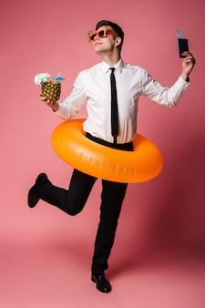 Красивый эмоциональный молодой бизнесмен с билетами и коктейлем