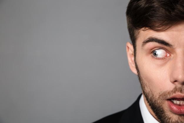 Обрезанный портрет испуганный молодой бородатый мужчина смотрит в сторону