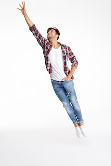 ジャンプカジュアルな魅力的な男性の完全な長さの肖像画