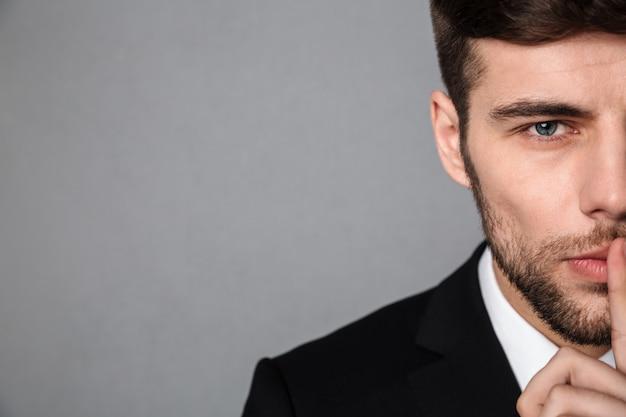沈黙のジェスチャーを示すクラシックジャケットでハンサムな若い男の写真をトリミング