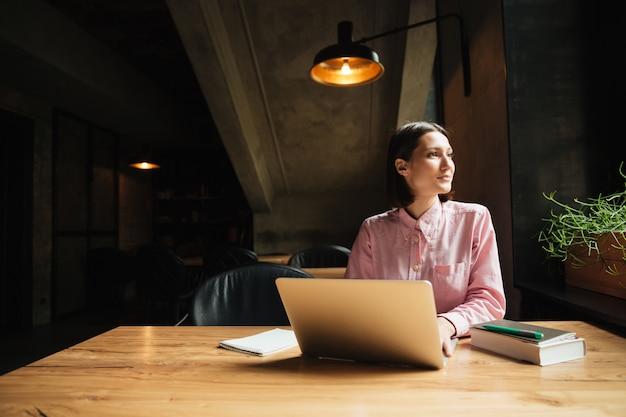 カフェのテーブルで座っている屈託のない物思いにふける女性