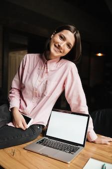 テーブルの上に座って幸せなブルネットの女性の垂直方向の画像