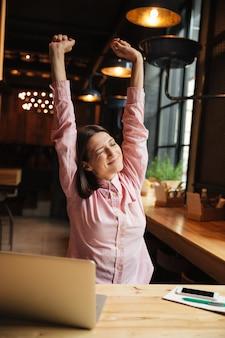 テーブルに座っている笑顔のブルネットの女性の垂直方向の画像