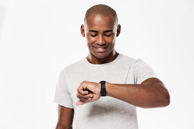 Счастливый молодой африканский человек, используя часы.
